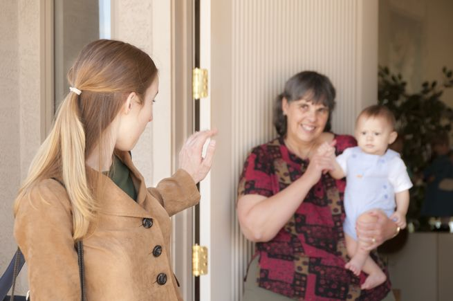 Young working mom waves goodbye to baby in sitter's arms at the door. Older woman could also be grandma.